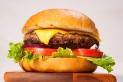 cheeseburger with lettuce, tomato, and onion on a brioche bun
