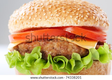 Cheeseburger with tomatoes and lettuce isolated on white