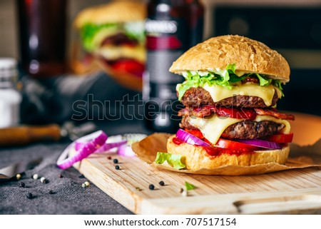 Cheeseburger with Two Beef Patties, Cheddar Cheese, Bacon, Iceberg Lettuce, Sliced Tomatoes and Red Onion on Cutting Board. Bottle of Beer and Some Ingredients on Table.