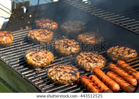 Cheeseburgers, hamburgers and hotdogs being grilled