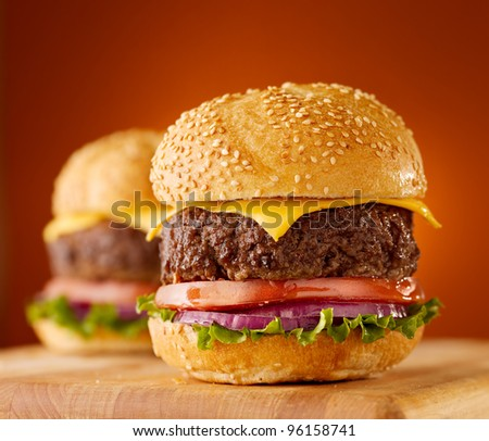 cheeseburgers on wooden board with lettuce, tomato and onion