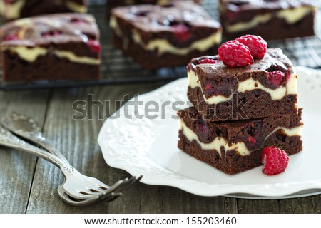 Cheesecake brownies with raspberry stacked on a plate