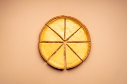 Cheesecake cutted in 8 equal slices, on a yellow table, minimal photography. World wide famous cheese dessert. Homemade sweet food.