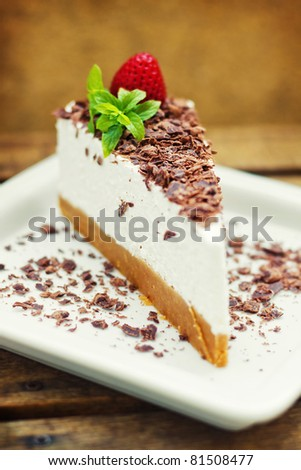 Cheesecake decorated with strawberry, mint and chocolate  (shallow dof)