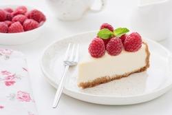 Cheesecake slice with raspberries on white plate. Slice of plain cheesecake. Raspberry cheesecake. Tasty cheesecake