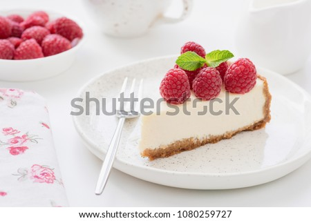 Cheesecake slice with raspberries on white plate. Slice of plain cheesecake. Raspberry cheesecake. Tasty cheesecake