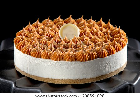 Cheesecake with caramel cream on black background