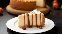Cheesecake with caramel sauce on black background. Tasty homemade caramel cheesecake