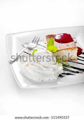 Cheesecake with whipped cream on white.