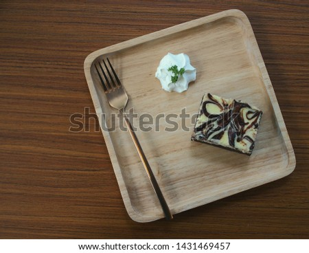 Cheesecakes and brass spoons in wooden trays for serving as snacks during break breaks