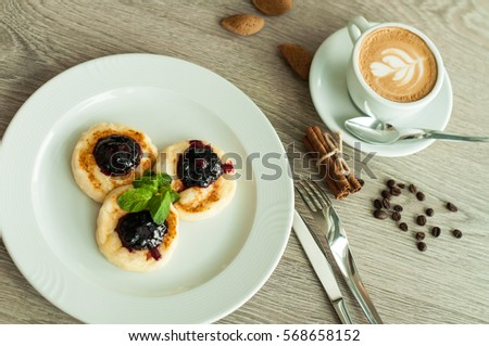 Cheesecakes for breakfast with jam and cappuccino coffee. banner for cafes and restaurants #568658152