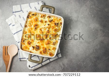 Photo of  Cheesy cauliflower casserole on concrete background. Top view, space for text, toned.