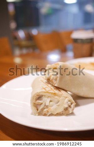Cheesy chicken warp on cafe table , Stock photo ©