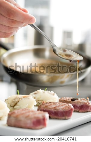 Chef add sause to a beef on professional kitchen