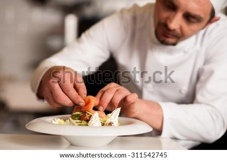 Chef adding topping for smoked salmon salad
