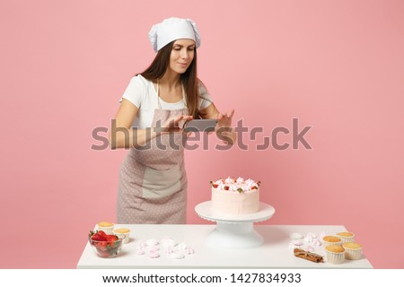 Chef cook confectioner or baker in apron white t-shirt, toque chefs hat cooking at table photographing cake for her blog isolated on pink pastel background in studio. Mock up copy space food concept