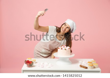 Chef cook confectioner or baker in apron white t-shirt, toque chefs hat cooking cake at table doing selfie on mobile phone isolated on pink pastel background in studio. Mock up copy space concept