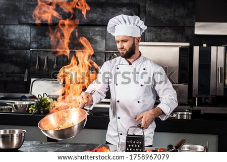 Chef cook food with fire at kitchen restaurant. Cook with wok at kitchen. Chef male in uniform hold wok with fire. Stock photo ©
