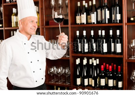 Chef cook hold glass of red wine in restaurant bar