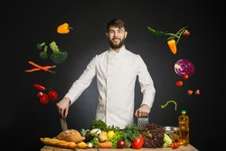 Chef cook in commercial kitchen. Professional chef stand on black background near the table with many fresh healthy fruits and vegetables. Happy smiling chef preparing meal with various vegetables