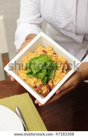 Chef cook showing a plate with her tasty  risotto, close-up