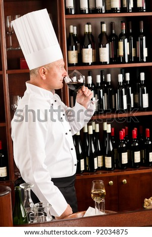 Chef cook smell glass of red wine in restaurant bar