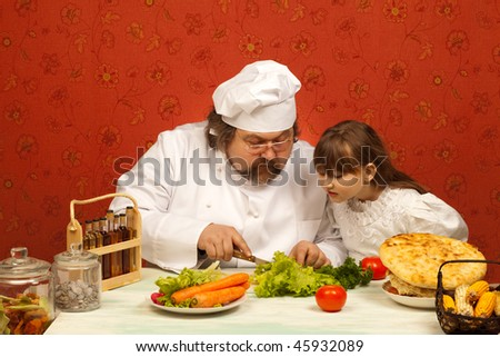 Chef cook teaching little girl to prepare salad