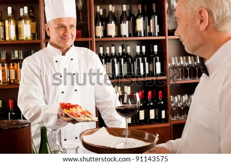 Chef cook with tapas waiter serve on tray in restaurant