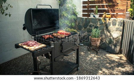 Chef cooking a delicious pork ribs with red peppers on the BBQ grill. Cook pork meat on grilled meat. Food cooked with grilling barbecue in backyard of house Photo stock ©