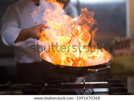 Chef cooking and doing flambe on food in restaurant kitchen Stock photo ©