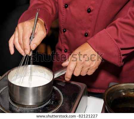 Chef cooking cream sauce on stove