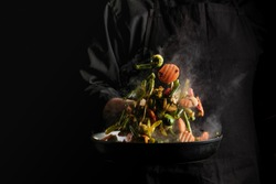 Chef cooking vegetables on a pan. Black background for copy text.