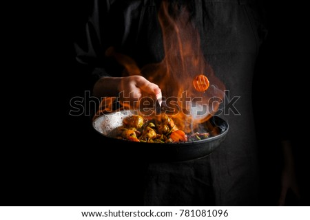 Chef cooking vegetables on a pan with fire flambe. Black background for copy text. Stock photo ©