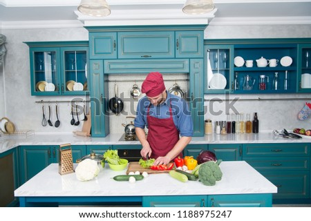 Chef cooking vegetarian recipe. Vegetarian cuisine rich vitamins. Man chef wear apron cooking in kitchen. Man cook vegetarian recipe with fresh vegetables. Vegetarian diet concept. Culinary recipe.