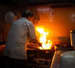 Chef cooking with fire in a hawker centre kitchen in Singapore
