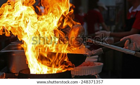 Chef Cooking With Fire In Frying Pan.\ Professional chef in a commercial kitchen cooking flambe style.\ Chef frying food in flaming pan on gas hob in commercial kitchen.