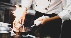 Chef cooking with flame in a frying pan on a kitchen stove, Chef in restaurant kitchen at stove with pan