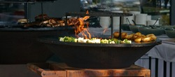 chef cooks broccoli, potatoes and meat at street food festival, barbeque. High quality photo