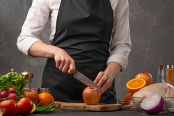 Chef cuts apples for cooking a duck or chicken. Recipe book, home recipes
