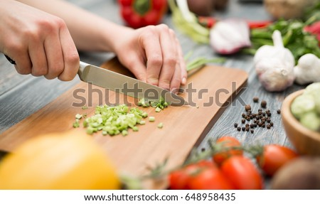 Chef cuts the vegetables into a meal. Preparing dishes. A woman uses a knife and cooks. ストックフォト ©