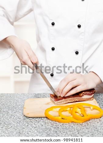 chef cutting bacon on board