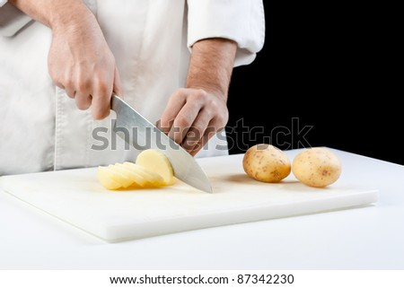 Chef cutting potatoes on black background