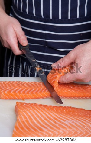 Chef cutting salmon fish on fillets with knife