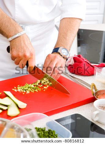 Chef cutting the zucchini on a board