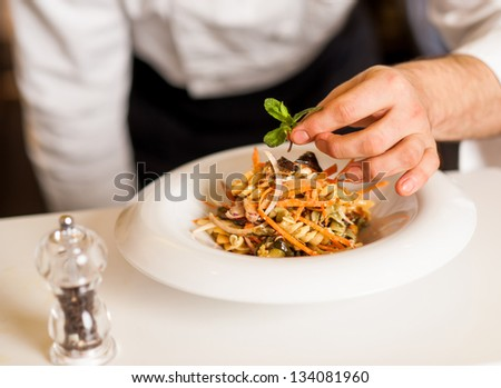 Chef dressed in white uniform decorating pasta salad, cropped image.