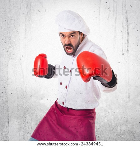 Chef fighting with boxing gloves over textured background #243849451