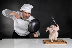 Chef fighting with knife and pan. Raw chicken attack