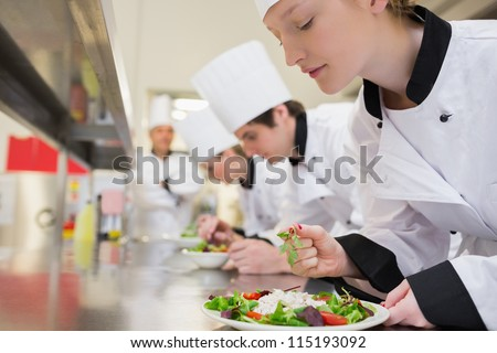 Chef finishing her salad in culinary class in kitchen Stock photo ©