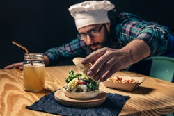 chef finishing up his vegan burger with lettuce tomato and sauce, fries with ketchup and healthy drink on a wooden table, vegetarian food and foodie lifestyle concept, selective focus