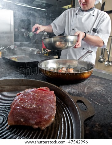Chef frying different courses on stove